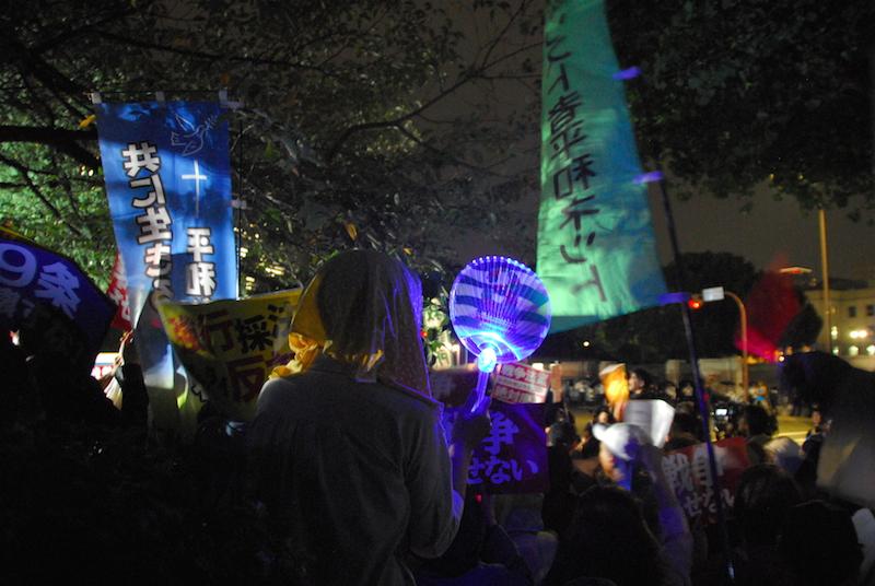 国会正門前付近で安保関連法案に反対する人々。右側の緑色の旗は平和を実現するキリスト者ネットワーク(キリスト者平和ネット)の旗で、左側の青色の旗は「共に生きる平和な世界」と記されたカトリック大阪大司教区社会活動センター(シナピス)の旗=16日夜<br />