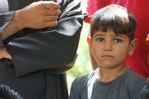 難民の男性たちが話す苦しみに耳を傾けるヤジディ教徒の少年(写真:世界福音同盟)