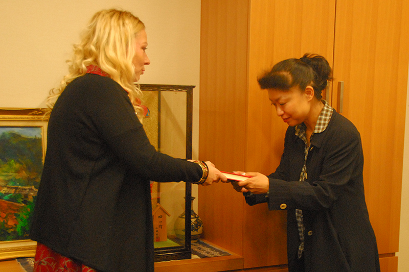 自身の回顧録『涙のあとは乾く』を、内閣大臣官房企画調整課長の西崎寿美氏(右)に手渡すキャサリン・ジェーン・フィッシャーさん=6日、衆議院議員第一会館内で