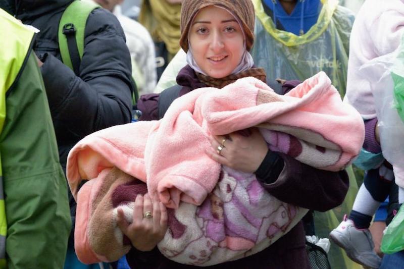 セルビアとクロアチアの国境付近で子どもを抱いている難民(写真:Paul Jeffrey)