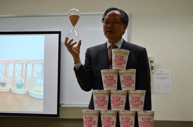 自社製品のカップ麺を前に「すべては神様の導きだった」と話す金森一雄さん=12日、船橋市勤労市民センター(千葉県船橋市)で