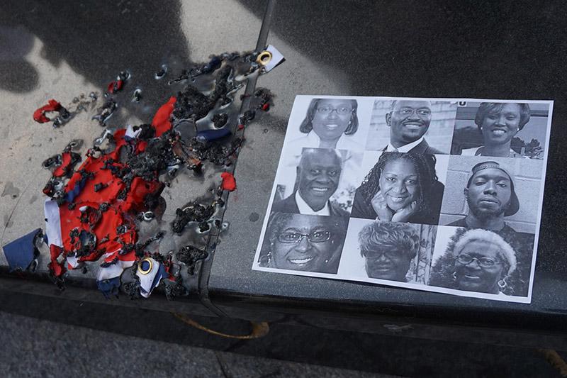 6月17日に米南部サウスカロライナ州チャールストン市にある黒人教会で発生した銃乱射事件で亡くなった男女9人の犠牲者の写真(右)と、抗議の意思を示して燃やされた南軍旗(写真:The All-Nite Images)