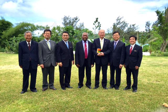 記念写真におさまるロンズデール大統領(中央)、日本国際飢餓対策機構の岩橋竜介理事長(左から3番目)、パン・アキモトの秋元義彦社長(右から3番目)ら=7日(写真:日本国際飢餓対策機構提供)
