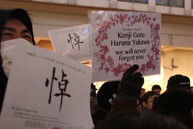 「悼」「in memory of Kenji Goto Yukawa Haruna we will never forget you」などと書かれたプラカードを持って、過激派組織「イスラム国」(IS)によって殺害された湯川遥菜(はるな)さんと後藤健二さんを追悼する集会に参加した人々=2015年2月8日、東京・渋谷駅前で