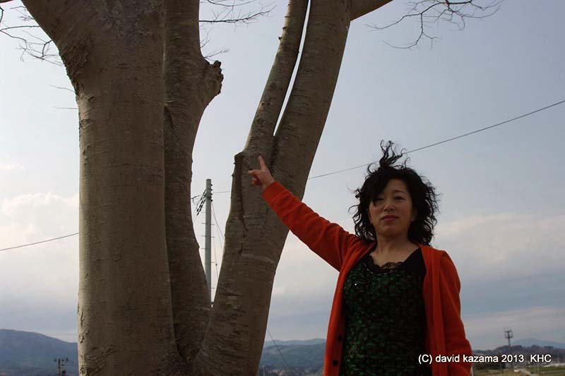三浦シュクンさんと、5年前、迫り来る津波に周り三方を囲まれ、逃げて来た数人と共に登ったけやきの木(写真:風間哲也氏提供)