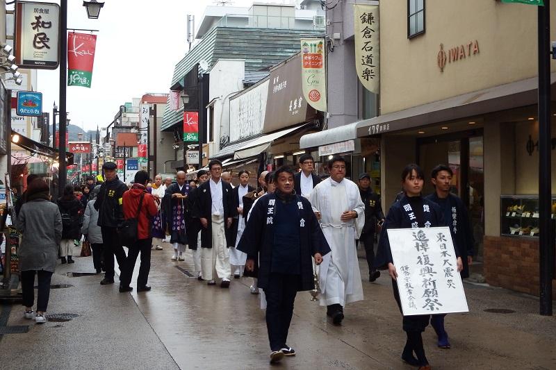 香炉を静かに振る山口道孝神父を先頭に、法螺貝を吹く僧侶、杓を持つ神職らと続く行列は、小町通りを抜けて鎌倉駅前を通過し、若宮大路にあるカトリック雪ノ下教会へと進んだ=11日、神奈川県鎌倉市で