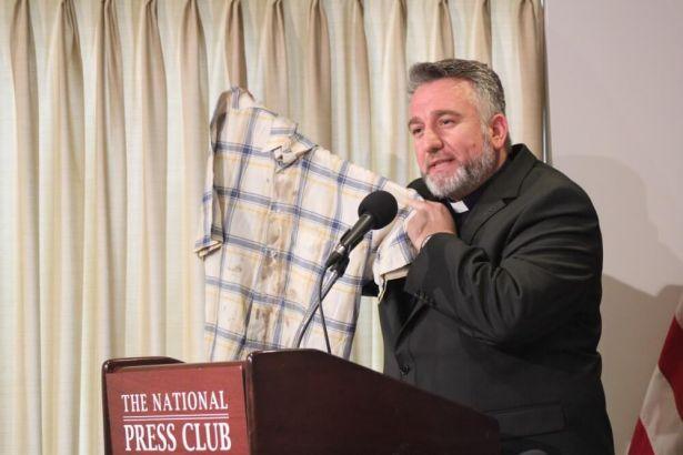 2006年にイスラム過激派によって誘拐され、9日間拘束されて拷問を受けた際に着用していた、血のシミの残るシャツを見せるカルデア人のダグラス・アル・バジ司祭=10日、ワシントンDCで(写真:クリスチャンポスト/Samuel Smith)