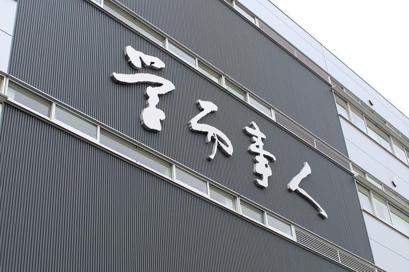 桜美林大学学而館(がくじかん)の町田街道側壁面に設置された「学而事人(がくじじじん)」の大サイン(写真:桜美林学園提供)