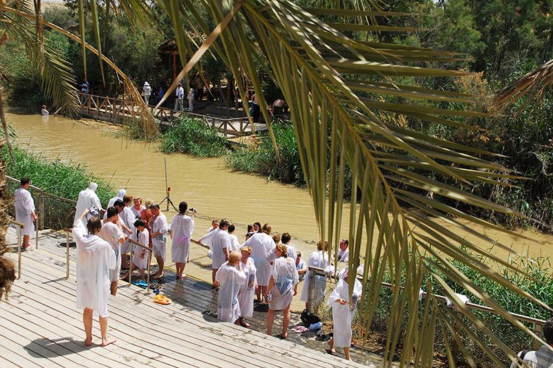 イエスが洗礼者ヨハネによって洗礼を受けた場所と考えられているヨルダン川のほとりで洗礼式に臨む人々(写真:udi Steinwell)