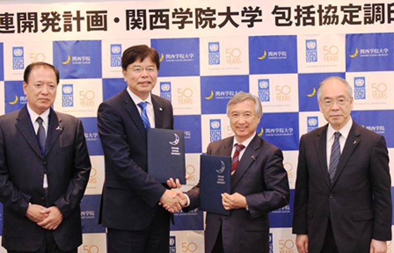 調印式で握手を交わす国連開発計画(UNDP)駐日代表の近藤哲生氏(写真中央左)と、関西学院大学学長の村田治氏(同右)=5月24日、ステーションコンファレンス東京(東京都千代田区)で