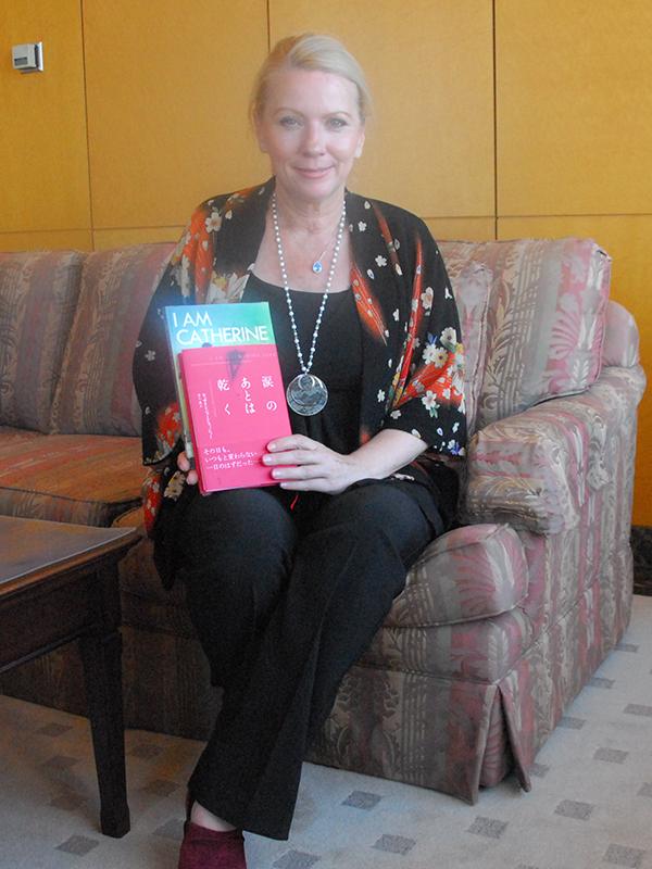昨年5月に講談社から出版された『涙のあとは乾く』と、その英語原書『I am Catherine Jane: The True Story of One Woman's Quest for Justice』を手にする著者のキャサリン・ジェーン・フィッシャーさん=2015年7月21日、講談社本社ビル(東京都文京区)で
