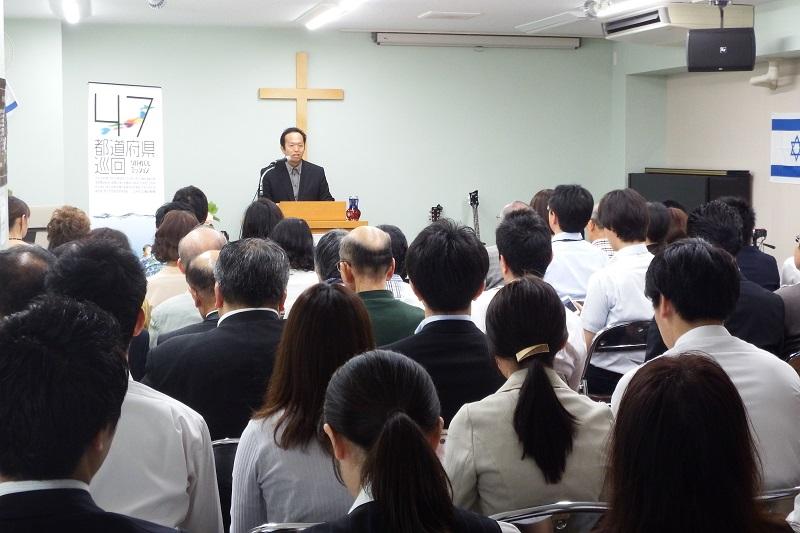 会場には地元の消防署や警察署、銀行などの職員も多数参加。「初めて教会に来た」という人だけでも約60人ほどが集まった。歓迎のあいさつを述べる炎リバイバル教会事務局長の篠原元さん=3日、同教会(東京都足立区)で