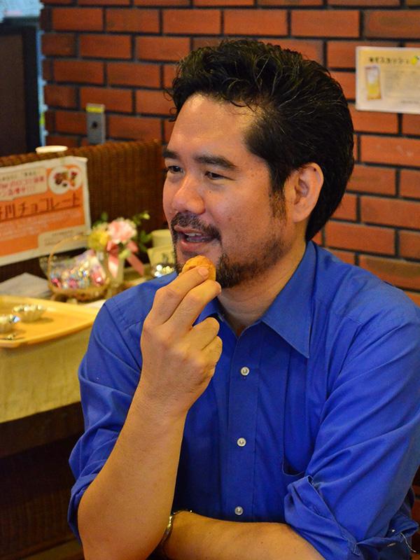 「3市YWCA沖縄デー『沖縄からのメッセージ』」で講演した平良愛香氏。講演後のティータイムで、サーターアンダギーを食べながら高校生らと談笑した=11日、横浜YWCAで