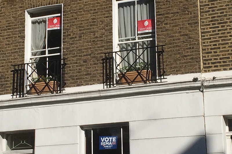 欧州連合(EU)からの離脱の賛否を問う国民投票への参加を呼び掛けるポスター。離脱を支持する赤いポスターと残留を支持する青いポスターが貼られている=21日、ロンドン中心部のピムリコで(写真:Philip Stevens)