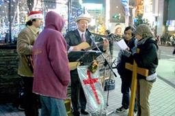 十字架を携えて輪になってクリスマスソングを歌う有志たち=25日、東京・新宿駅東口のアルタ前で