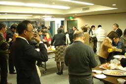 フライデーナイト終了後、ロビーで軽食を囲み歓談する参加者たち=同上