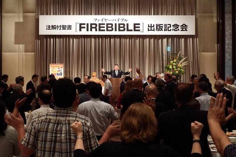 記念会では、出版のために尽力した人々・支援者への感謝の祈り、献納と日本の祝福の祈りがささげられた。参加者一同も立ち上がって、ステージ上に積み上げられた日本語版ファイヤーバイブルに手を差し向け、共に声を上げて祈りをささげた=2日、京王プラザホテル(東京都新宿区)で