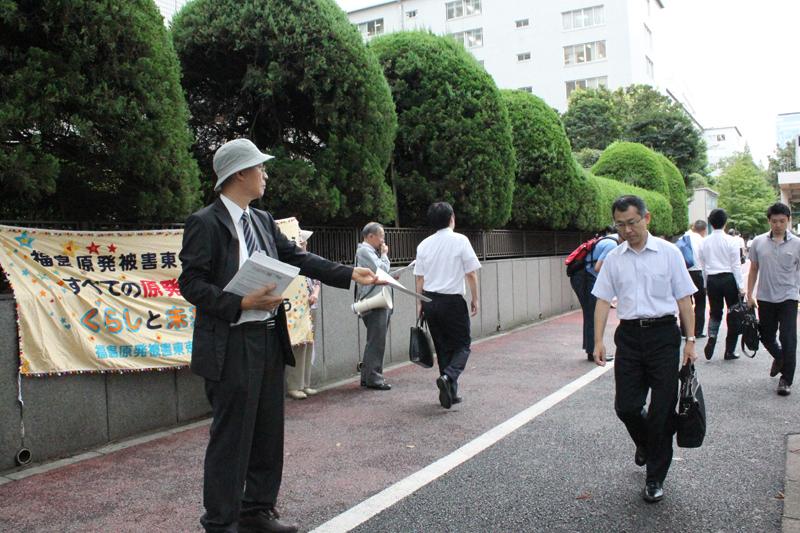 チラシを配り、福島原発被害東京訴訟の裁判傍聴を呼び掛ける支援者たち=14日、東京地方裁判所前で