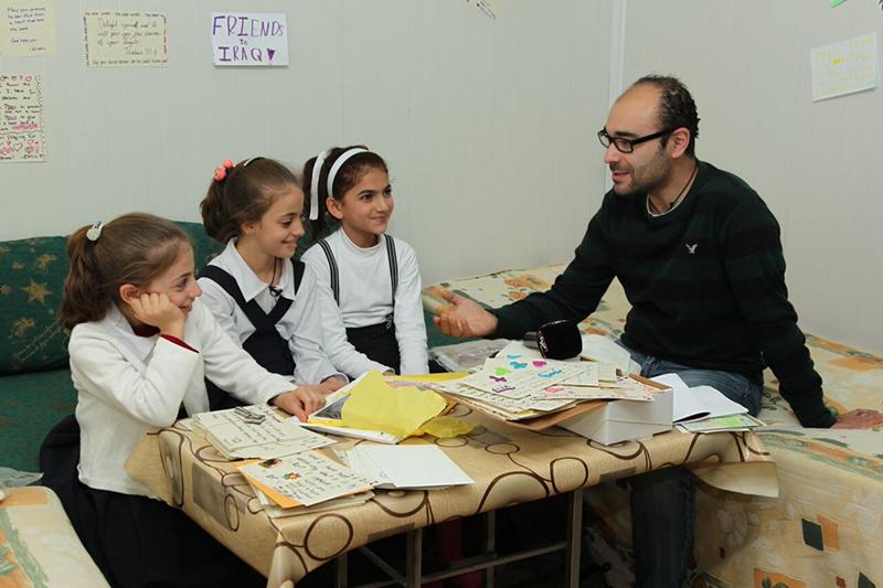 姉妹と友人に挟まれて笑顔でインタビューに応えるミリアムちゃん(左中央)=イラク・アルビルで(写真:SAT−7)