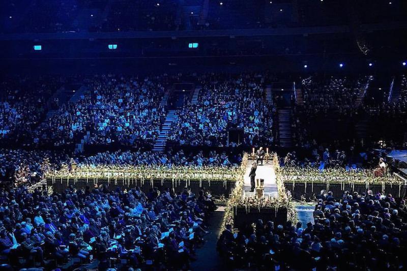 スウェーデン南部の都市マメルにある多目的アリーナ「マルメ・アリーナ」で行われたルーテル、カトリック両教会の宗教改革共同記念行事で、十字架型のステージ上で力強い希望の証しを語る、南スーダン難民のローズ・ナシケ・ロコニェンさん(写真手前)=10月31日、(写真:ルーテル世界連盟 / A. Danielsson)