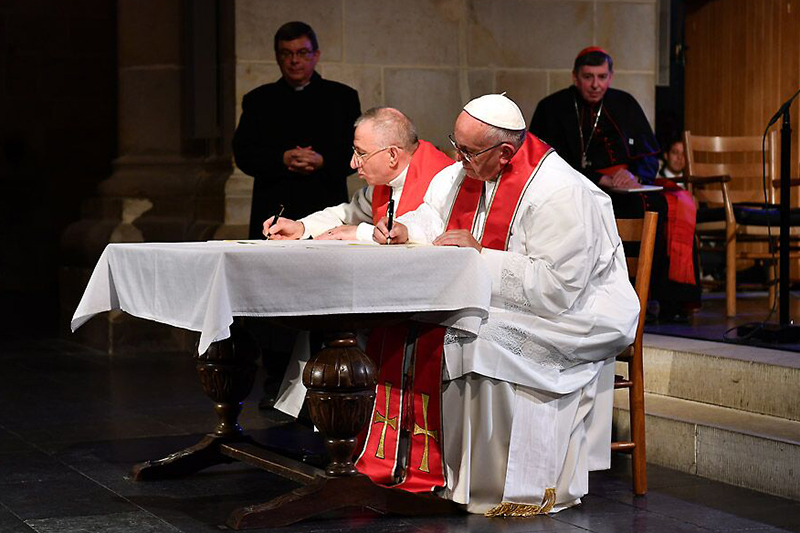 共同声明に署名するルーテル世界連盟(LWF)議長のムニブ・ユナン監督(中央左)とローマ教皇フランシスコ(中央右)(写真:Magnus Aronson / Ikon)