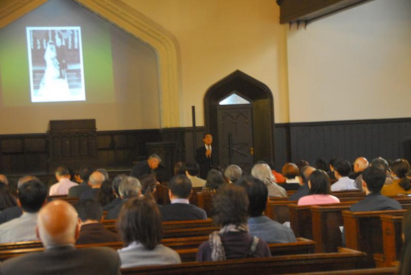 スライドにW・M・ヴォーリズと一柳満喜子の結婚式記念写真(写真左上)を映し出して講演する芹野与幸氏(同中央奥)=5日、東京都港区の明治学院礼拝堂で(本紙記者が同学院の許可を得て撮影)