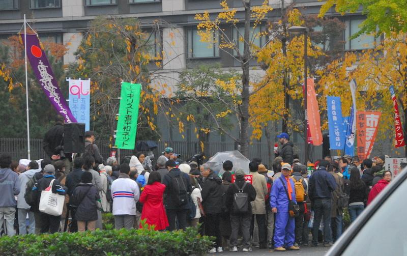 19日午後2時から3時半まで国会議員会館前から国会図書館前路上(東京都千代田区)にかけて行われた、総がかり行動実行委員会主催の「安倍政権の暴走止めよう!自衛隊は戦地に行くな!11・19国会議員会館前行動」のステージ付近の様子。主催者発表で3800人がこの行動に参加した。左から2つ目の旗は日本カトリック正義と平和協議会、3つ目はキリスト者平和ネット。