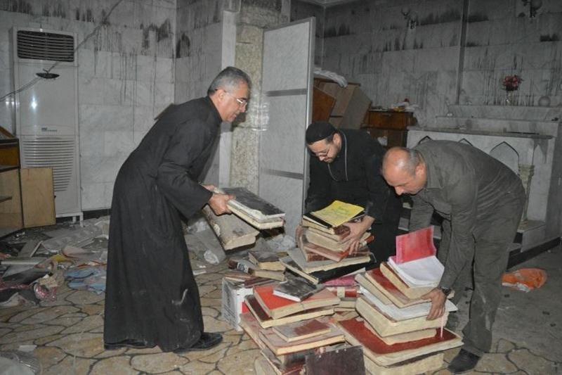 過激派組織「イスラム国」(IS)の支配から解放された、イラク北部の町バーテリアにあるマート・シモニー・シリア正教会で、荒らされた教会内を整理するキリスト教の聖職者ら(写真:ア・デマンド・フォー・アクション=ADFA)<br />