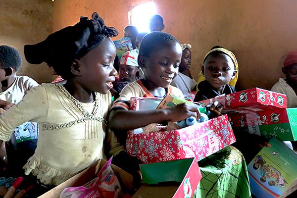 プレゼントがいっぱいに詰まった靴箱を開けて喜ぶ子どもたち(写真:サマリタンズ・パース)