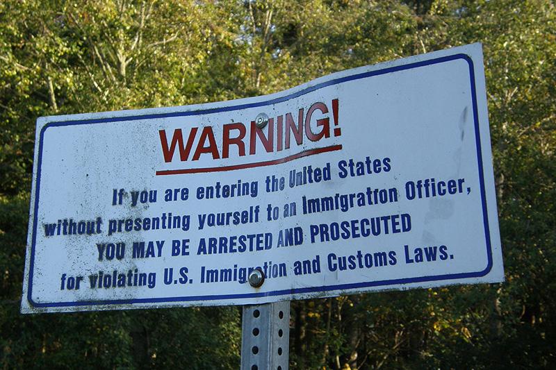 米国とカナダの国境近くに立つ不法入国を警告する標識(写真:Makaristos)