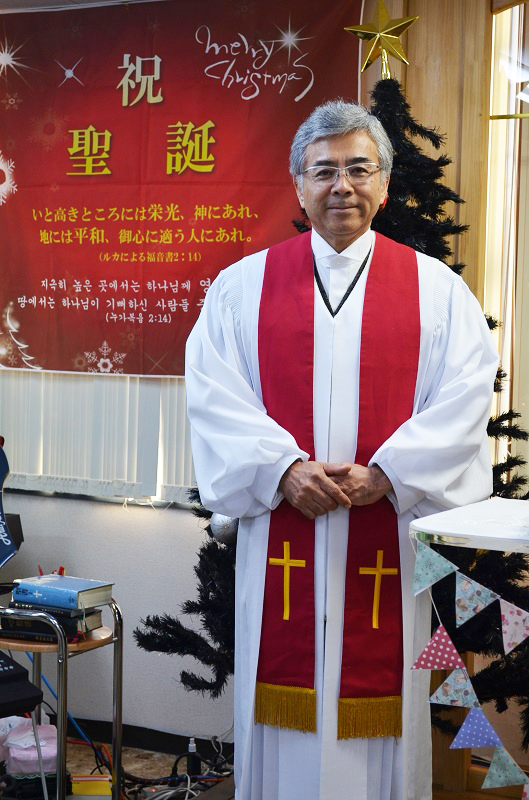「地域の無料イベントに参加するような気持ちで教会へ」と純福音成田教会の妹尾光樹牧師は話す。「クリスマスには、このような格好の牧師が教会で説教を行います。ガウンの色などは教団教派によって違います」