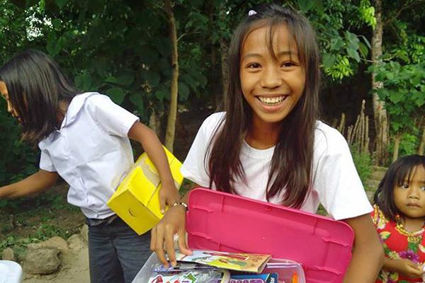日本から贈られたシューボックスを受け取り、笑顔を見せるフィリピンの女の子(写真:サマリタンズ・パース)