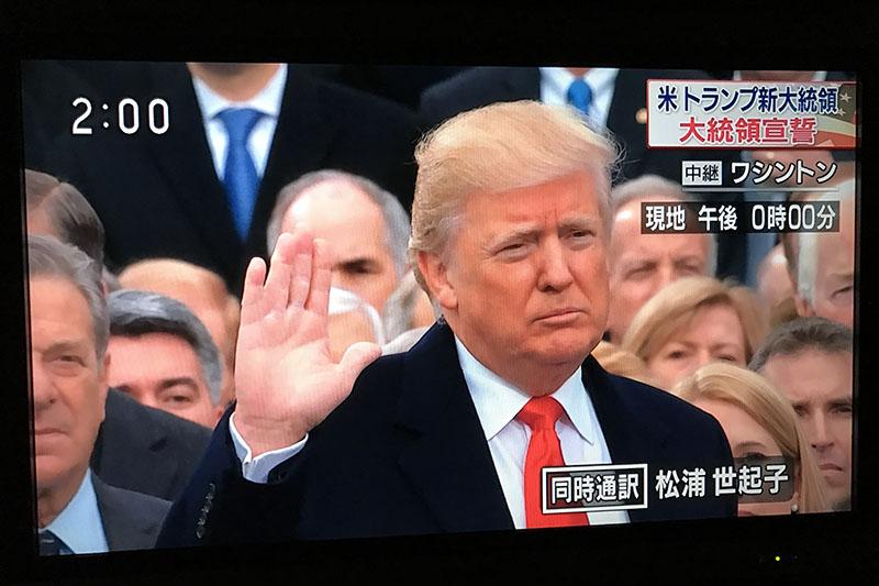 テレビ画面に映し出される、就任式で宣誓するトランプ新大統領=21日