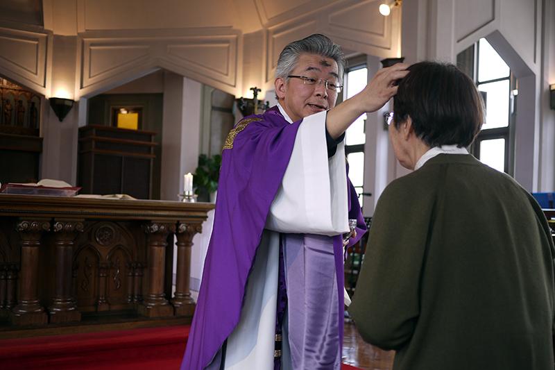 信者一人一人の額に灰で十字のしるしを付ける稲川圭三主任司祭。紫色の祭服は四旬節に入ったことを表す=1日、カトリック麻布教会(東京都港区)で