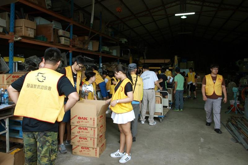 手際よく協力して食料を段ボール箱から出すボランティアたち=2016年9月14日、台湾・台中市南投県竹山で