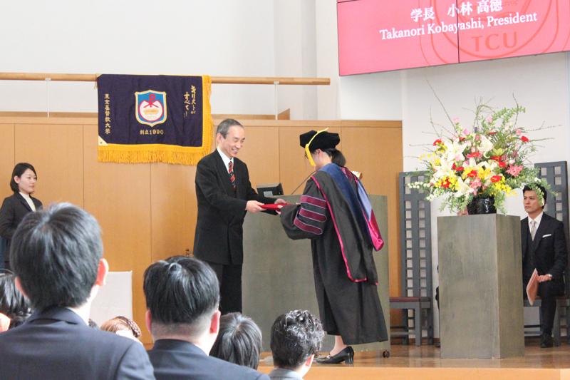 小林高徳学長から学位記を受け取る東京基督教大学(TCU)初の博士課程修了者=10日、同大(千葉県印西市)で