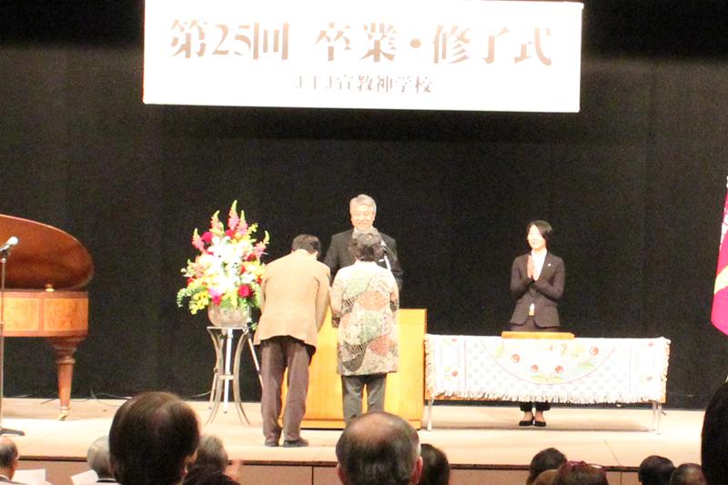 証書授与で、横山英実学長から卒業証書を受け取る卒業生。年齢、学びの期間はさまざま=20日、YMCAアジア青少年センター(東京都千代田区)で