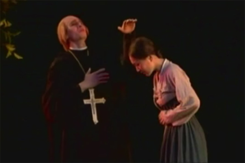 西洋人風の神父とみられる男性が母親に近づく場面