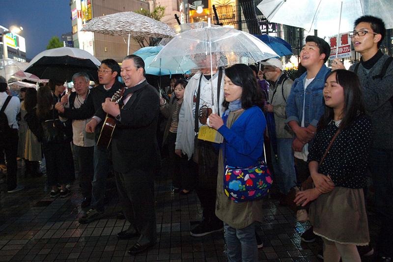 ギターを演奏するのが菅野直基牧師=22日、東京・新宿で