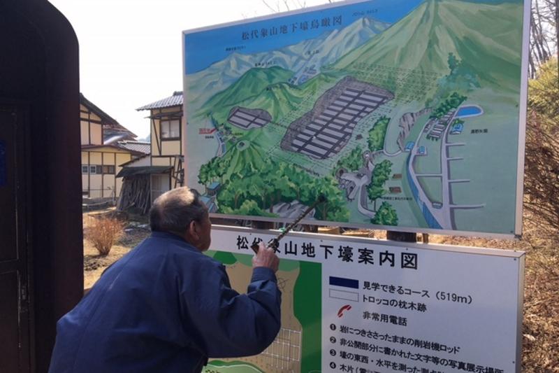 案内図を見ながら当時を思い出す野沢貞雄さん。看板の中央左手には、天皇住居が皆神山に建設されたことが示されており、実際に現在もそれは未使用のまま残されている=3月5日、松代象山地下壕(長野県長野市松代町)で