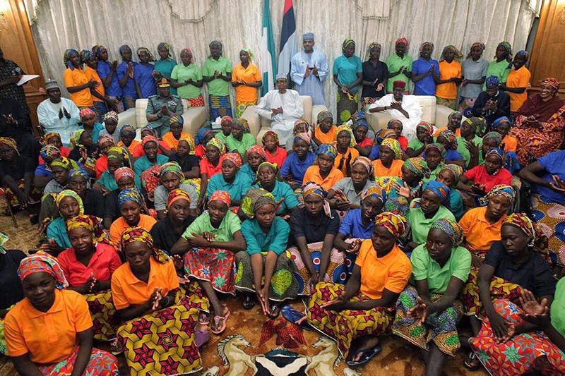 イスラム過激派組織「ボコ・ハラム」から解放され、ムハマドゥ・ブハリ大統領(中央後方)と面会した少女たち(写真:同大統領の側近、バシール・アフマド氏のツイッターより)