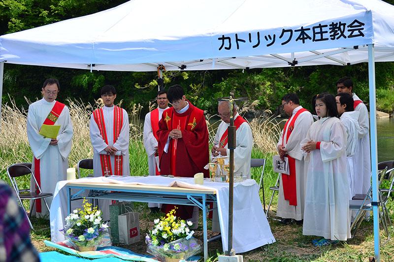 カトリック教会の司祭、助祭の7人の他、県内外からカトリック教徒を中心に約200人が参加=3日、神流川河川敷