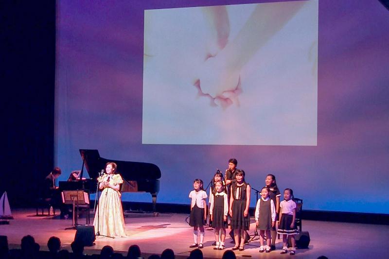 ソプラノの日比野愛子さんと一緒に歌うジョイキッズ。その背後には、人が生まれてから天に帰るまでをイメージした映像が映し出された。(写真:日比野音療研究所提供)