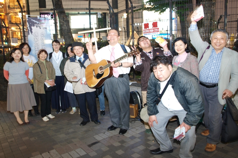 ギターを持つ菅野直基氏と、路傍伝道を行うメンバーたち=15日、東京・新宿で
