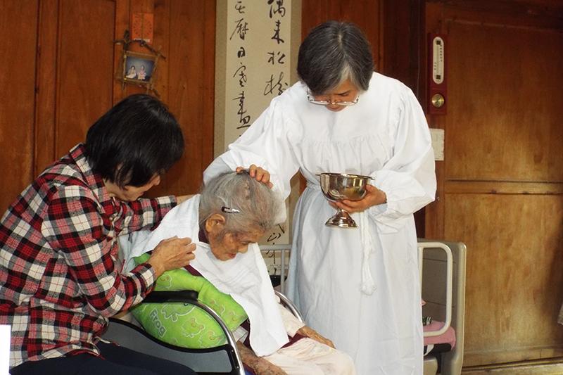 新川代利子牧師(右)の2番目の姉(左)に支えられて洗礼を受ける新川ハルさん。102歳9カ月での洗礼だった=2016年12月30日、沖縄県西原町の自宅で(写真:新川牧師提供)