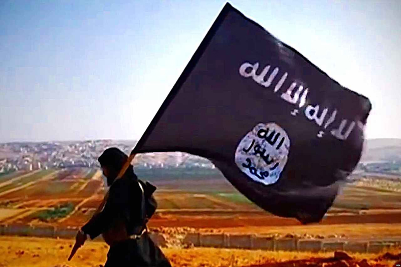 「イスラム国」(IS)の黒い旗を掲げて歩くISの戦闘員(写真:ボイス・オブ・アメリカ)