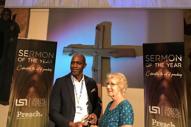 ロンドン神学院(LST)のカルビン・サミュエル校長(左)から、優勝トロフィーを手渡されるキャロル・ホジキンスさん=6月22日、LSTで