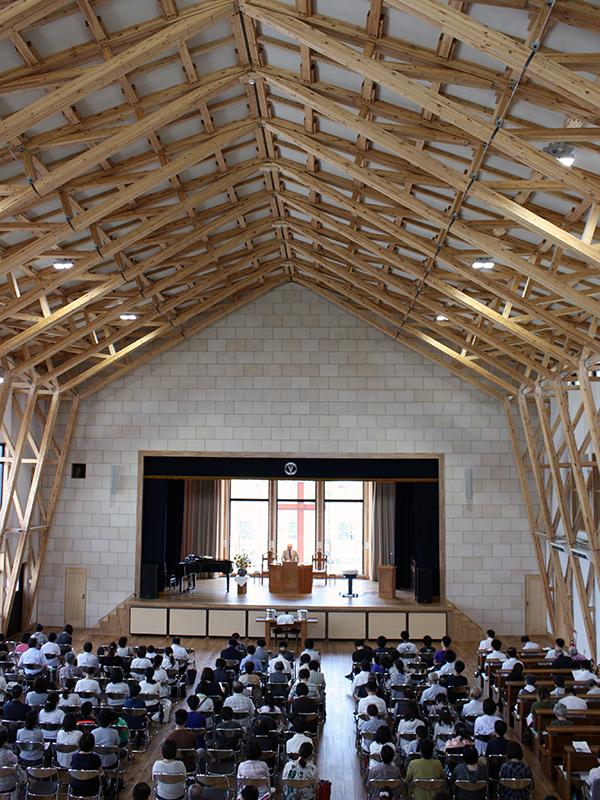 5月に献堂式を行ったばかりの木造の新会堂「グローリア礼拝堂」の大礼拝堂。400人が共に礼拝にあずかれる広さで、講壇の後ろのカーテンが開かれると、ガラス越しに庭の十字架が現れる(2日、岡山市で)
