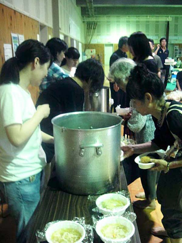 今回の豪雨で、朝倉市立杷木中学校に避難した人たちに食事を提供するボランティアたち(写真:神戸国際支縁機構提供)