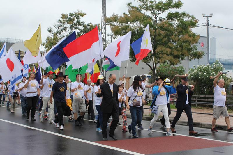 世界各国の国旗、王であるイエスを表すライオンの旗、ジーザス・レインズのロゴマークを掲げた色とりどりの旗、イスラエルの旗などを持った人たちが連なり、角笛(ショーファー)を吹き鳴らし、「ジーザス・レインズ」を叫びながら行進した=15日、豊洲ピット(東京都中央区)で